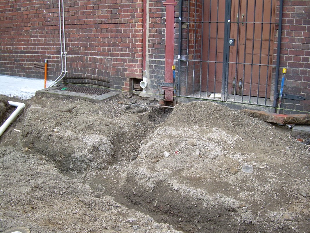 A channel is dug for pipes that will collects water from the downpipes and divert it into the system.